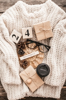 Tasse mit kaffee, gläsern, zapfen auf einem pullover