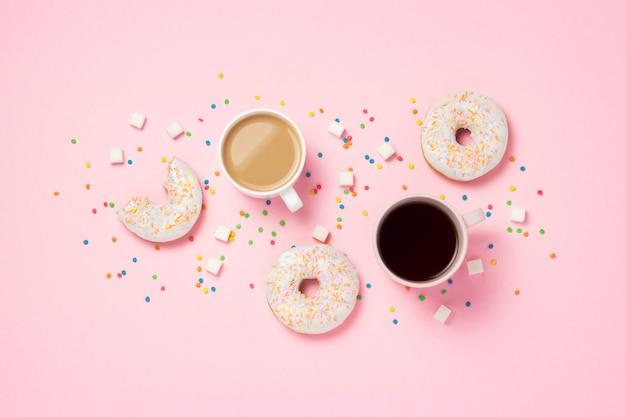Tasse mit kaffee oder tee, frische leckere süße donuts, bunte dekorative bonbons, zuckerwürfel auf einem rosa hintergrund. bäckereikonzept, frisches gebäck, leckeres frühstück, fast food. flache lage, draufsicht.