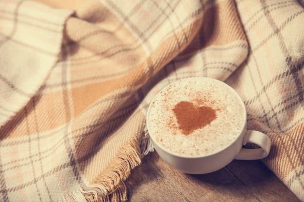 Tasse mit kaffee und form des kakaoherzens darauf und schal
