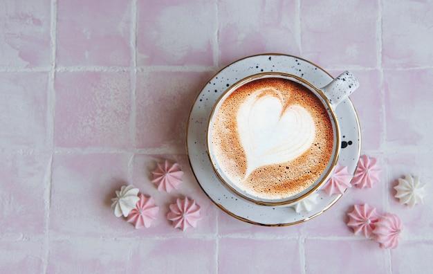 Tasse mit kaffee und kleinen baisers auf einer gefliesten oberfläche