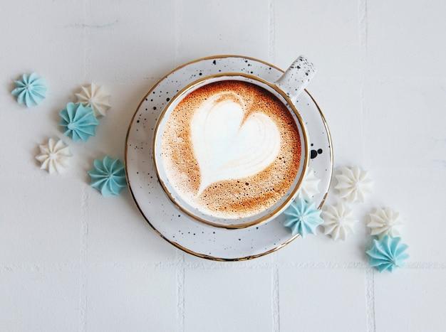 Tasse mit kaffee und kleinen baisers auf gekacheltem hintergrund