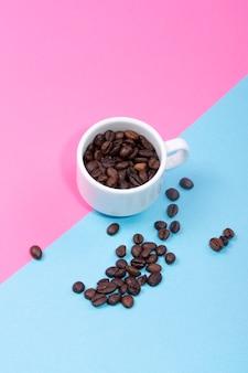 Tasse mit kaffeebohnen an einer farbigen wand