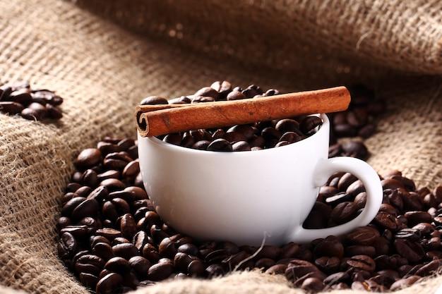 Tasse mit kaffeebohnen und zimtstange