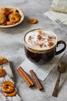 Tasse mit kakao oder kaffee mit milchzimt und keksen auf hellgrauer oberfläche