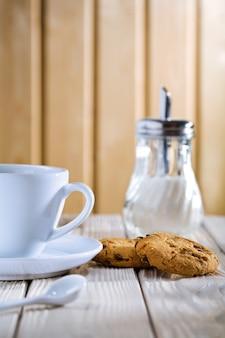 Tasse mit keksen und zuckerspender