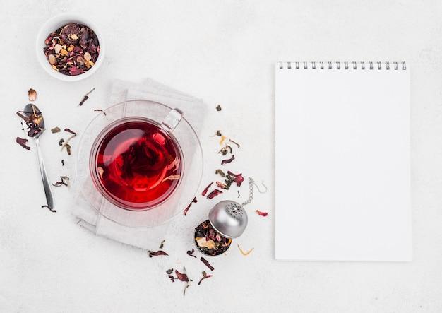 Tasse mit kräutertee und notizbuch