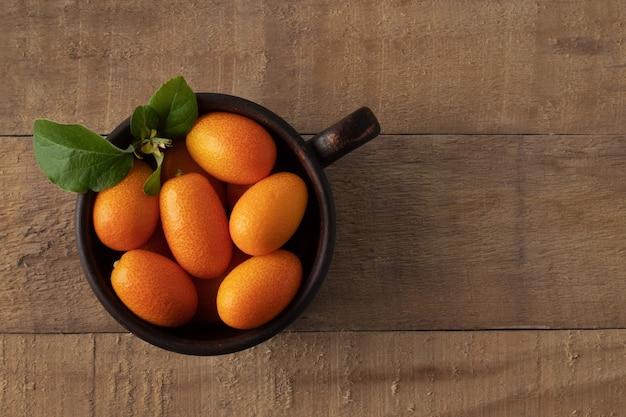 Tasse mit kumquatfrüchten auf hölzernem hintergrund, draufsicht. speicherplatz kopieren