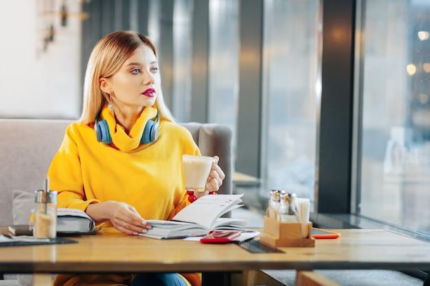 Tasse mit latte. schöne blauäugige frau, die eine tasse mit leckerem latte hält, während sie in der cafeteria sitzt