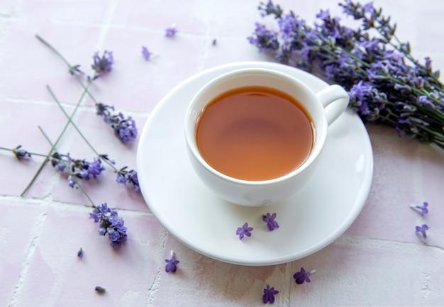 Tasse mit lavendeltee und frischen lavendelblüten auf rosafarbenem fliesenhintergrund
