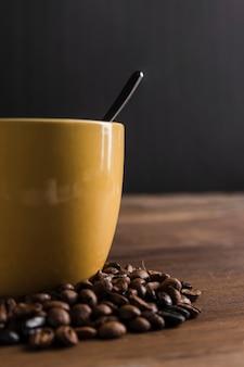 Tasse mit löffel in der nähe von kaffeebohnen