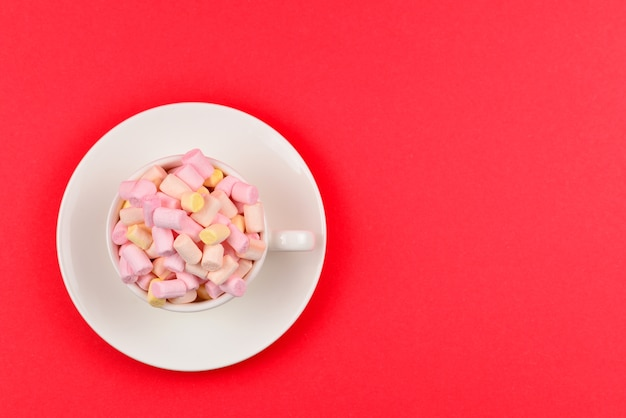 Tasse mit marshmallow auf rotem grund. speicherplatz kopieren.