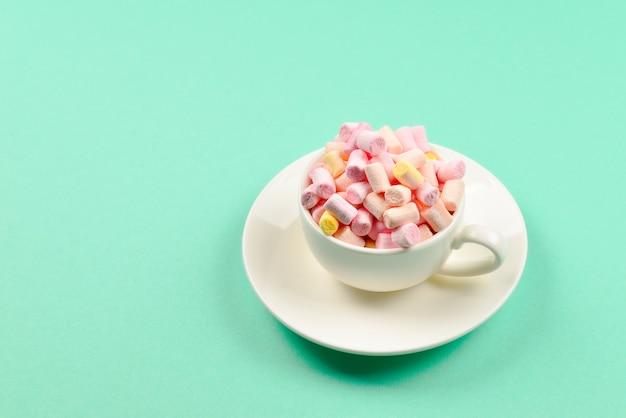 Tasse mit marshmallows auf blauem grund