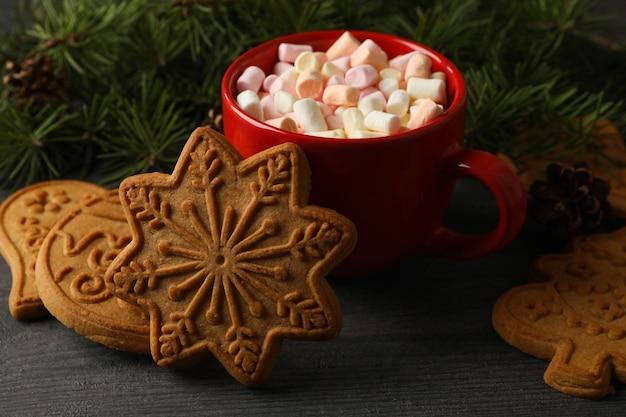Tasse mit marshmallows und weihnachtsplätzchen auf dem tisch