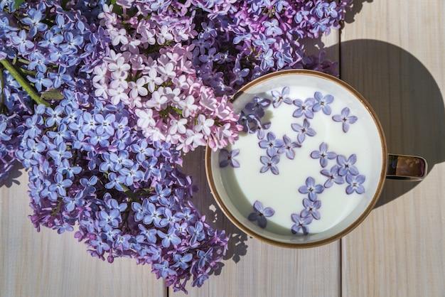 Tasse mit milch und kleinen lila lila blüten