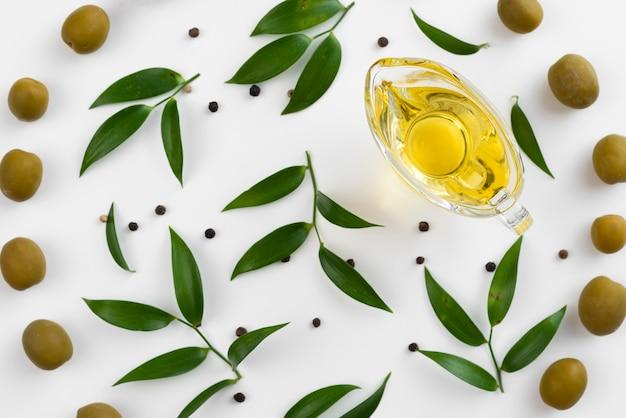 Tasse mit olivenöl, umgeben von blättern und oliven