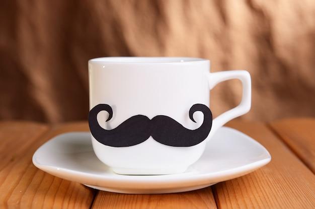 Tasse mit schnurrbart auf tisch auf brauner oberfläche
