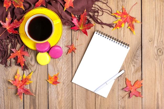 Tasse mit schwarzem kaffee, gelben lutschern, makronen, notizblock, holztisch mit herbst gefallenen orangenblättern