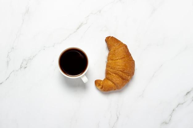 Tasse mit schwarzem kaffee und croissant auf einem marmortisch