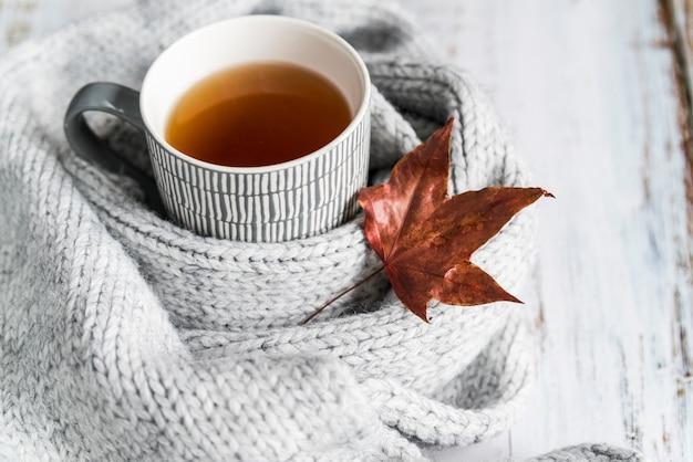 Tasse mit tee in gestricktem schal mit ahornblatt