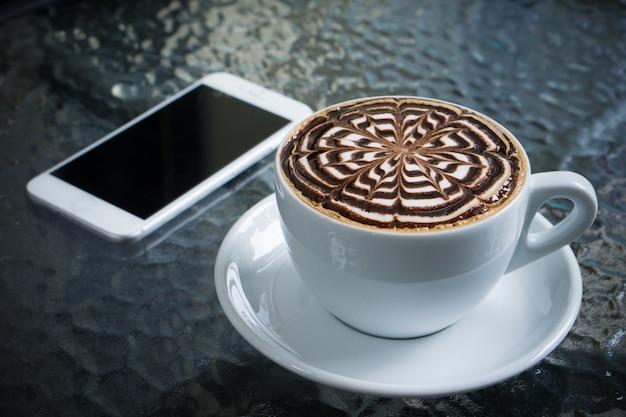 Tasse mokka auf dem tisch mit smartphone