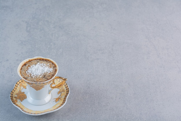 Tasse schaumigen heißen kaffee auf steinhintergrund.
