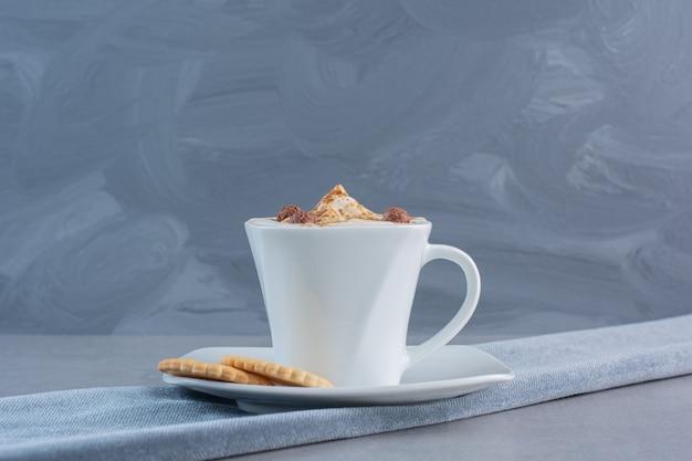 Tasse schaumigen heißen kaffee und kekse auf steintisch.