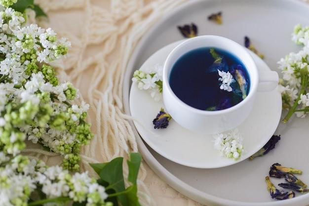Tasse schmetterlingserbentee (erbsenblüten, blaue erbse) für gesundes trinken, entgiftungsgetränk und weißen flieder.