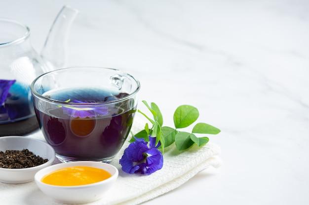 Tasse schmetterlingserbsenblumentee mit honig auf tisch