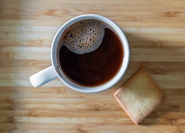 Tasse schwarzen hausgemachten kaffee und keks auf der tischplattenansicht