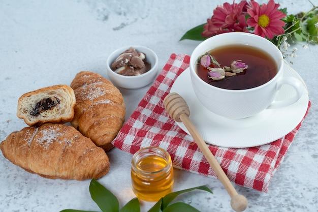Tasse schwarzen heißen tee und frisch gebackene croissants gefüllt mit schokolade.