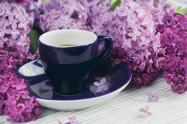 Tasse schwarzen kaffee, lila blumen auf hellem holztisch