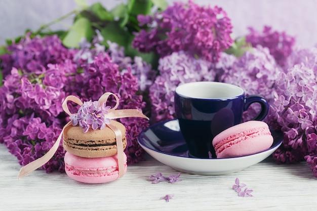 Tasse schwarzen kaffee, lila blumen und süße pastellfranzösische makronen auf hellem holztisch