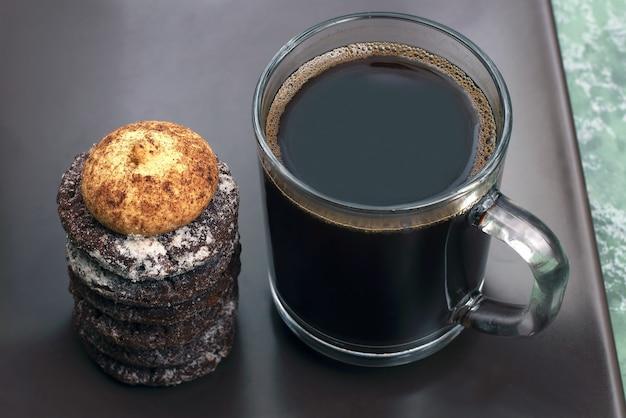 Tasse schwarzen kaffee mit keksen auf einem dunklen teller
