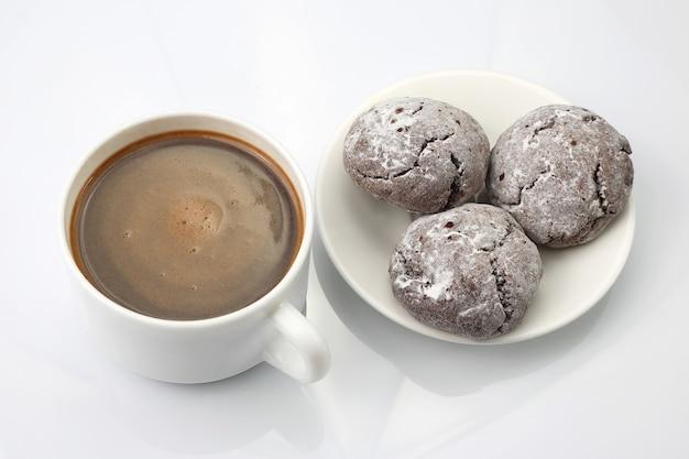 Tasse schwarzen kaffee mit keksen auf weiß