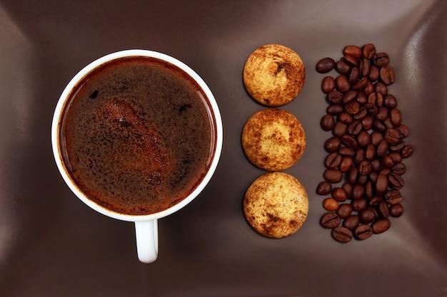 Tasse schwarzen kaffee mit keksen und bohnen auf einem dunklen teller