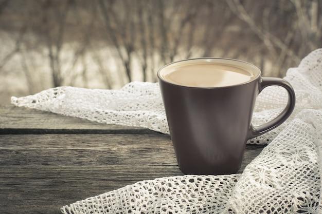 Tasse schwarzen kaffee mit milch vor dem fenster und einer spitze auf dem holz