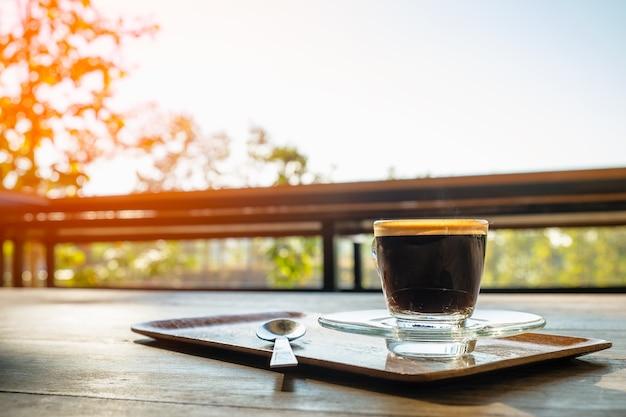 Tasse schwarzen kaffee mit schaum auf einem tisch.