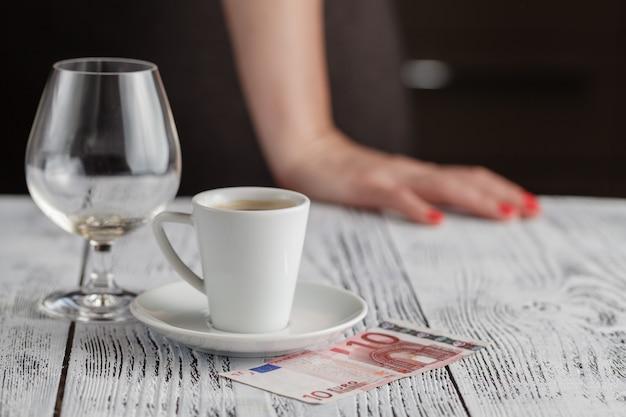 Tasse schwarzen kaffee und euro-banknoten