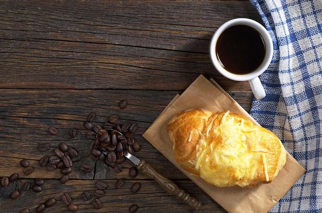 Tasse schwarzen kaffee und frisches croissant mit käse zum frühstück auf dunklem holztisch, draufsicht. platz für text