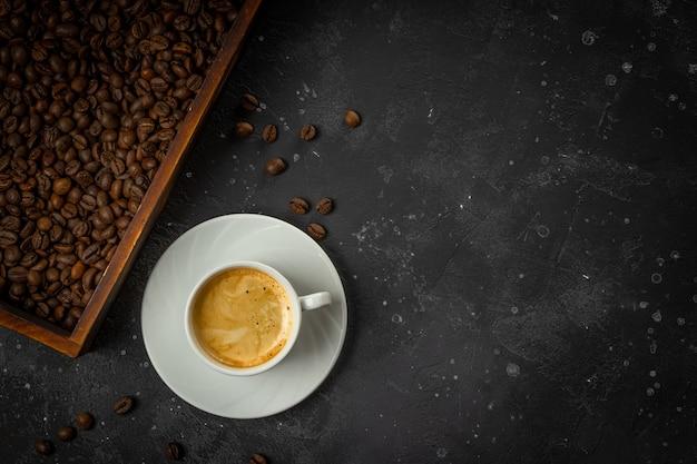 Tasse schwarzen kaffee und geröstete kaffeebohnen in einer holzkiste auf einem dunkelgrauen hintergrund