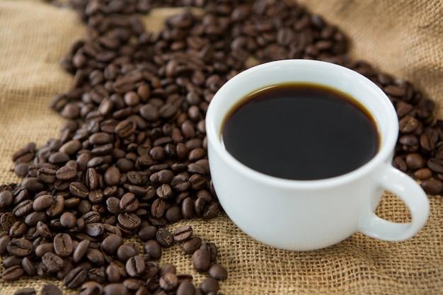 Tasse schwarzen kaffee und geröstete kaffeebohnen