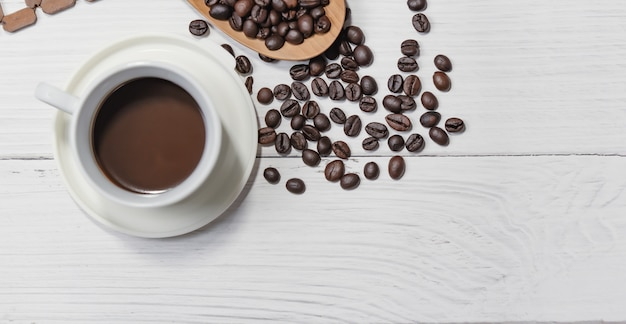 Tasse schwarzen kaffee und kaffeebohnen gute essentials auf weißem holztisch. draufsicht.