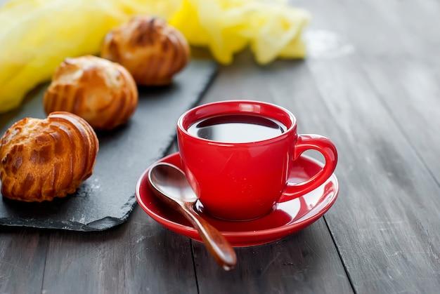 Tasse schwarzen kaffee und kleine französische eclairs