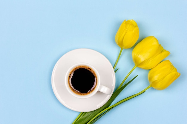 Tasse schwarzen kaffees auf einer untertasse und einem blumenstrauß gelbe tulpenblumen auf einer blauen hintergrundoberansicht