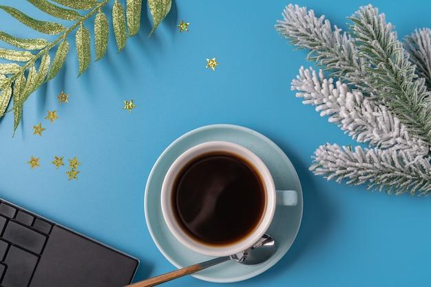 Tasse schwarzen kaffees, zweig des neujahrsbaums und der tastatur auf blauem hintergrund, flache lage. weihnachtskonzept. Premium Fotos