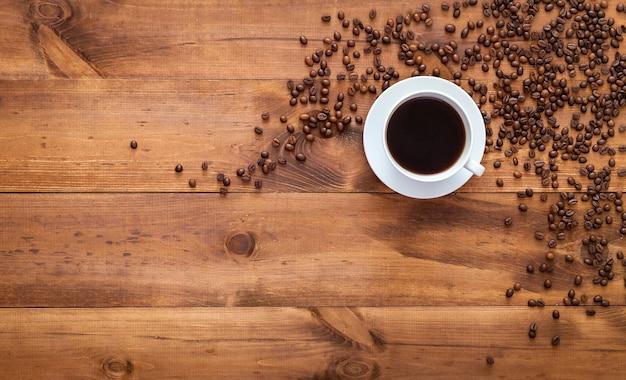 Tasse schwarzen morgenkaffee und kaffeebohnen, die auf braunem holztisch verstreut sind, dunkler espresso dunkler kaffeearoma-café-ladenhintergrund, warmes heißes getränkgetränk im becher, draufsicht, flache lage, nahaufnahmekopierraum