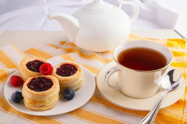 Tasse schwarzen tee mit dänischem gebäckkuchen mit preiselbeermarmelade und frischer blaubeere und himbeere