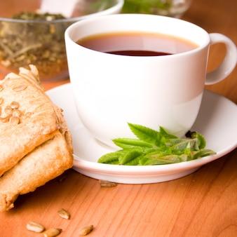 Tasse schwarzen tee mit kräutern und brot