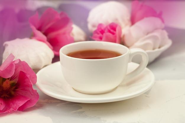 Tasse schwarzen tee mit marshmallows und rosa blüten
