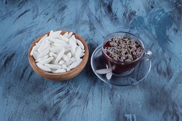 Tasse schwarzen tee mit schüssel mit weißen bonbons auf steinoberfläche.